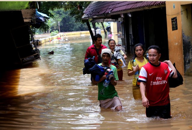 Residents make their way through a flooded neighborhood in Jakarta, Indonesia, Tuesday, February 10, 2015. Heavy downpour has caused flooding throughout the city. (Photo by Tatan Syuflana/AP Photo)