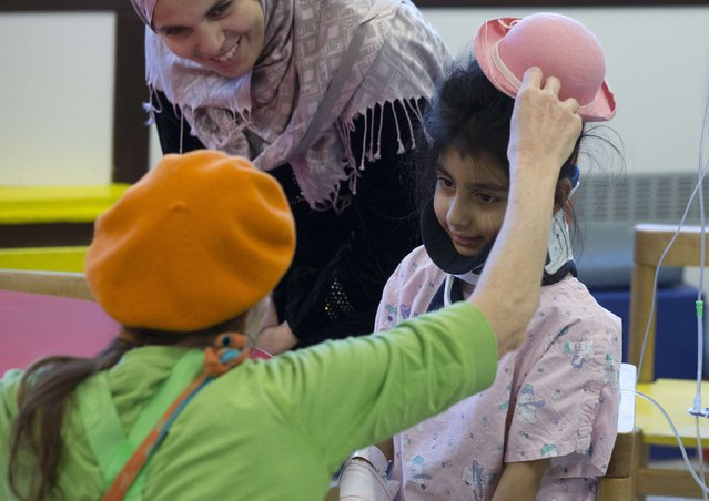 Belgian clown Rondelle adjusts the hat of Zeinab from Lebanon at the pediatric department of the Hopital Erasme at the Universite Libre de Bruxelles (ULB), in Brussels January 20, 2015. (Photo by Yves Herman/Reuters)