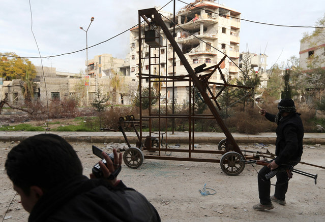 """A """"Free Syrian Army"""" fighter uses a catapult to fire a homemade grenade at Syrian Army soldiers during a fight in the Arabeen neighborhood of Damascus, on January 24, 2013. (Photo by Goran Tomasevic/Reuters)"""