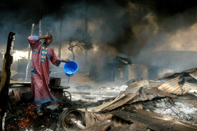 A man rinses soot from his face at the scene of a gas pipeline explosion near Nigeria's commercial capital Lagos in this December 26, 2006 file photo. Up to 500 people were burned alive when fuel from a vandalised pipeline exploded in Nigeria's largest city. Hundreds of residents of the Abule Egba district went to scoop fuel using plastic containers after thieves punctured the underground pipeline overnight to siphon fuel into a road tanker, locals said. (Photo by Akintunde Akinleye/Reuters)