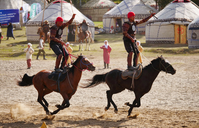 Riders stand atop their horses as they speed past the crowds. (Photo by Amos Chapple/Radio Free Europe/Radio Liberty)
