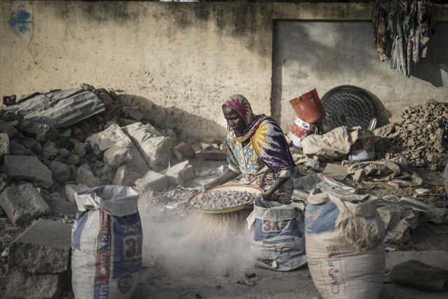 Habiba, a gravel crusher who thinks she is between 50 and 60 years old, sifts with an improvised sieve to separate gravel from sand near the Cite International des Affaires in N'Djamena, on April 12, 2021. In the heart of N'Djamena, the capital of Chad, dozens of women surrounded by a swarm of ragged and often skeletal children, along a road or on a huge adjacent vacant lot, without a single shaded point, crush concrete, cement or brick blocks twelve hours a day. (Photo by Marco Longari/AFP Photo)