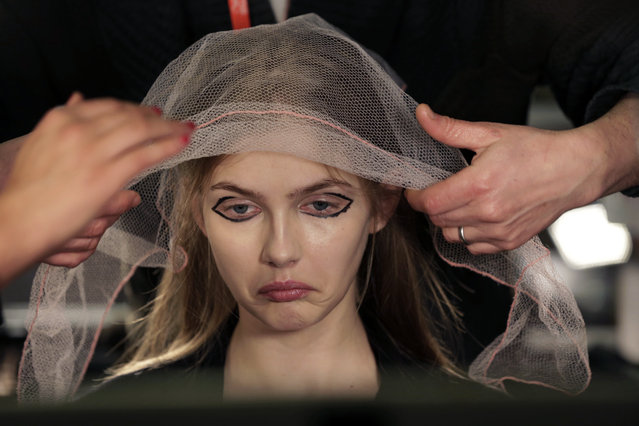 A model has her hair styled backstage before the DKNY Fall 2015 collection is modeled, during Fashion Week, in New York, Sunday, February 15, 2015. (Photo by Richard Drew/AP Photo)