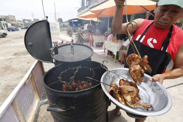 Cayo Malpartida cooks chicken and pork on a makeshift grill fashioned out of an oil barrel at Rendon Restaurant in Lurin, on the outskirts of Lima, February 15, 2015. (Photo by Mariana Bazo/Reuters)
