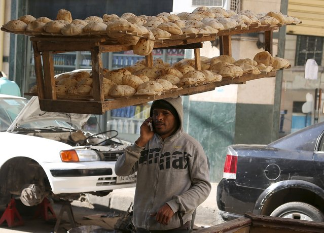 An employee of a bakery talks on his mobile while balancing on his head a tray of freshly baked bread from a local bakery in a street in Cairo, Egypt, January 12, 2016. (Photo by Asmaa Waguih/Reuters)