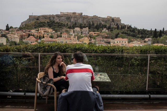 A man and a woman drink coffee in the Monastiraki district of Athens,with the ancient Acropolis hill in the background, Monday, May 3, 2021. Cafes and restaurants have reopened in Greece for sit-down service for the first time in nearly six months, as the country began easing coronavirus-related restrictions with a view to opening to the vital tourism industry in the summer. (Photo by Petros Giannakouris/AP Photo)