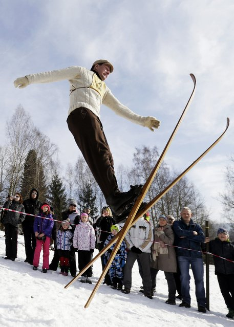 A participant jumps on vintage skis during a traditional historical ski race in the northern Bohemian town of Smrzovka February 21, 2015. (Photo by David W. Cerny/Reuters)