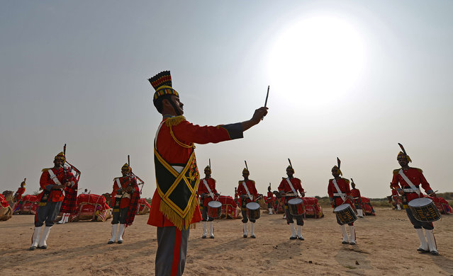 In this photograph taken on November 13, 2015, Band Major of Pakistan Desert Rangers, Muhammad Iqbal (C) conducts his team members before they mount on camels for a march in Moj Garh, some 100 kilometres east of Bahawalpur in Punjab Province. A haunting peal reminiscent of the Scottish Highlands reverberates across Pakistan's inhospitable Cholistan desert as what is believed to be the world's only camel-mounted military bagpipe band marches, noses in the air. (Photo by Aamir Qureshi/AFP Photo)