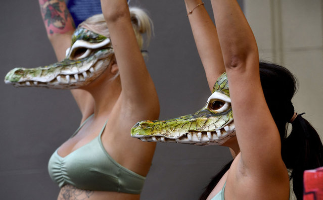 Activists from the animal rights group PETA, wearing bikinis and crocodile masks, stand outside a store of the French fashion label Hermes in Melbourne on March 16, 2021, to protest against their use of crocodile skins and the recent purchases by Hermes and LVMH of crocodile farms in Australia's Northern Territory. (Photo by William West/AFP Photo)