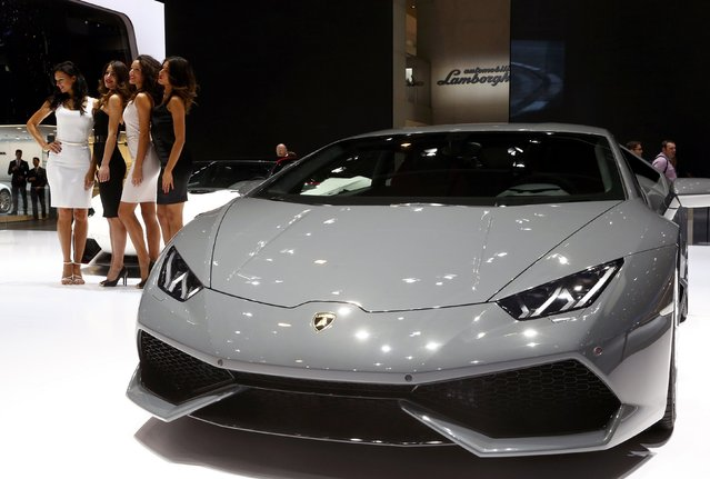 Models pose between a Lamborghini Aventador LP 700-4 and a Lamborghini Huracan LP 610-4 (R) during the second press day ahead of the 85th International Motor Show in Geneva March 4, 2015.  REUTERS/Arnd Wiegmann
