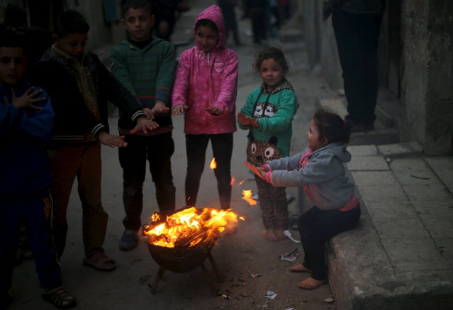 Palestinian children warm themselves by a fire on a stormy day at Shati (beach) refugee camp in Gaza City January 18, 2016. (Photo by Mohammed Salem/Reuters)