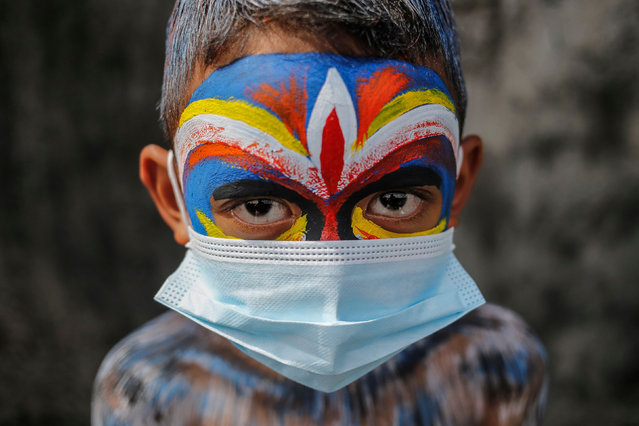 Balinese have their bodies painted and wears protective mask during sacred Ngerebeg ritual amid COVID-19 pandemic at Tegallalang Village in Gianyar, Bali, Indonesia on May 19 2021. Ngerebeg is a sacred ritual held every six month which is believed to expel bad luck and evil spirits. The participants decorates their bodies with colourful paints and accessories to symbolise astral beings while marching across the village. (Photo by Johanes Christo/NurPhoto/Rex Features/Shutterstock)