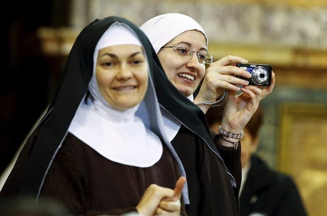 A nun takes a picture as Pope Francis arrives at the Naples' Duomo during his pastoral visit in Naples March 21, 2015. (Photo by Stefano Rellandini/Reuters)