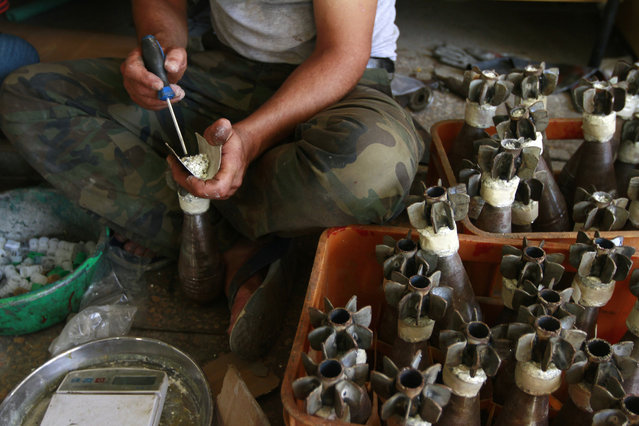 A Free Syrian Army fighter makes improvised mortar shells at a weapons factory in Aleppo, September 4, 2013. (Photo by Hamid Khatib/Reuters)