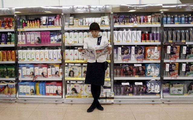 A saleswoman looks at a newspaper as she waits for customers in front of hair products at a supermarket in Seoul in this April 27, 2011 file photo. South Korea is expected to report inflation figures this week. (Photo by Truth Leem/Reuters)