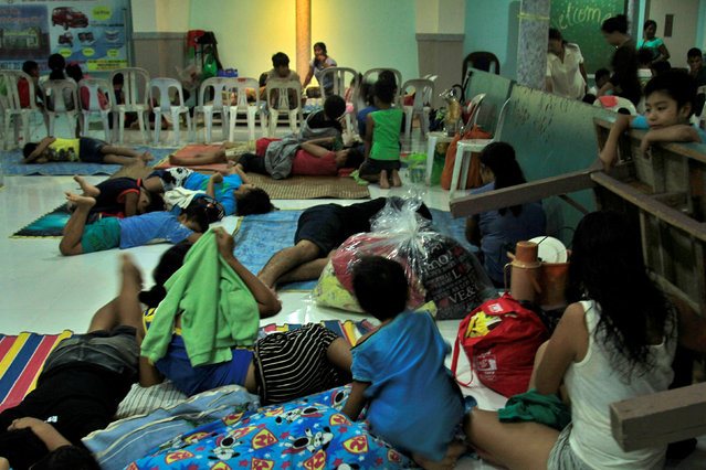 Residents celebrating Christmas Day at the evacuation center take a break before Typhoon Nock-ten is expected to strike Legazpi City, Albay province, central Philippines December 25, 2016. (Photo by Reuters/Stringer)