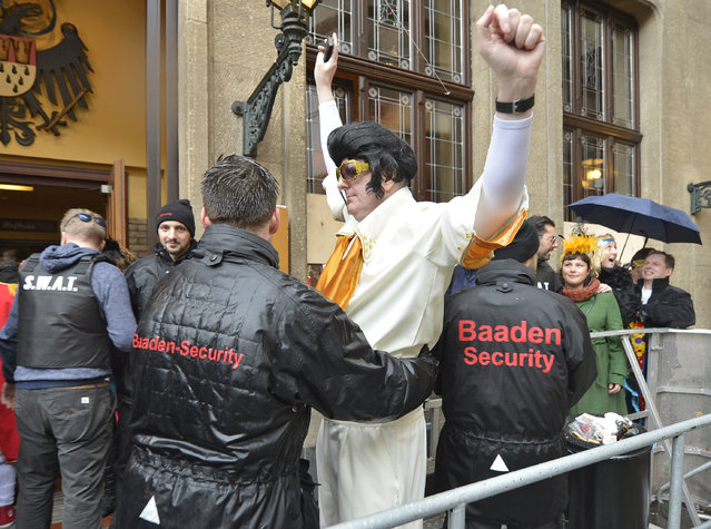 Security checks a  reveler  costumed as Elvis in front of a pub during the start of the street carnival in Cologne, Germany, on Thursday, February 4, 2016. (Photo by Martin Meissner/AP Photo)