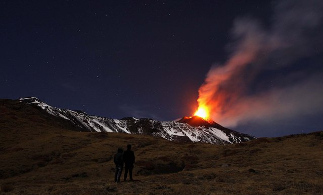 People watch Italy's Mt. Etna spewing lava as it erupts on the southern island of Sicily. (Photo by Antonio Parrinello/Reuters)
