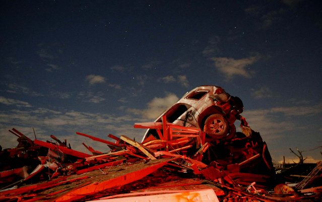 A vehicle sits on a pile of debris from the destruction caused by a tornado that touched down in Washington, Illinois, on November 17, 2013. A fast-moving storm system triggered multiple tornadoes on Sunday, killing at least five people, injuring about 40 and flattening large parts of the city as it tore across the Midwest. (Photo by Jim Young/Reuters)
