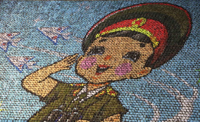 "North Korean students use different colored cardboard to form a picture of a child in uniform as a background during a mass gymnastic and artistic performance ""Arirang"", in Pyongyang July 26, 2013. The games are the world's biggest choreographed extravaganza, part circus act, part rhythmic gymnastics floor, with plenty of reverence for the late North Korean leader Kim Jong-il. (Photo by Jason Lee/Reuters)"