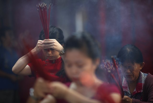 People pray with joss sticks at Dharma Bhakti Temple on the first day of the Lunar New Year in Jakarta, Indonesia February 8, 2016. (Photo by Darren Whiteside/Reuters)