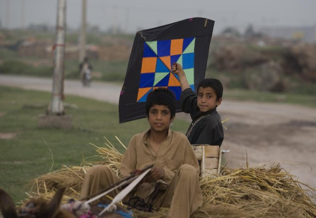Pakistani children, who are displaced from tribal areas where security forces are currently  fighting against militants, carry kites as they ride a cart  in Islamabad's slums, Friday, March 27, 2015 in Pakistan. (Photo by B. K. Bangash/AP Photo)