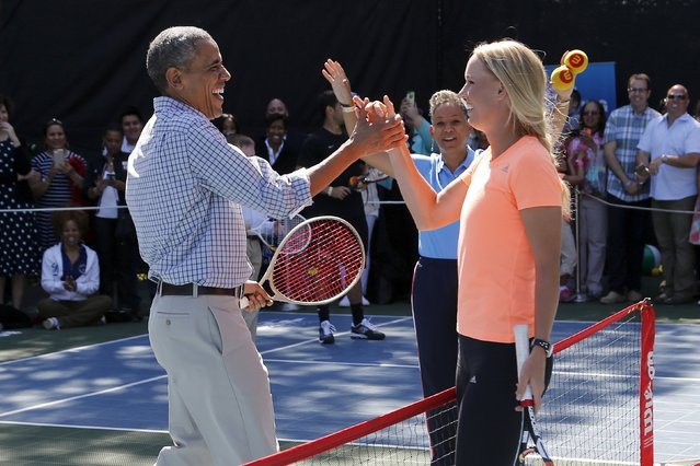 U.S. President Barack Obama (L) reacts to hitting a winner down the line against a tough volley from tennis player Caroline Wozniacki (R), one of the activities at the annual Easter Egg Roll at the White House in Washington April 6, 2015. (Photo by Jonathan Ernst/Reuters)