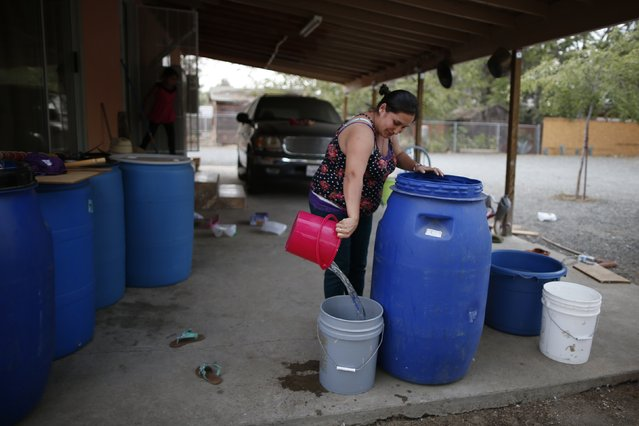 Marisela Corona, 26, whose well has run dry, pours water from a tank on her back porch in Porterville, October 14, 2014. (Photo by Lucy Nicholson/Reuters)