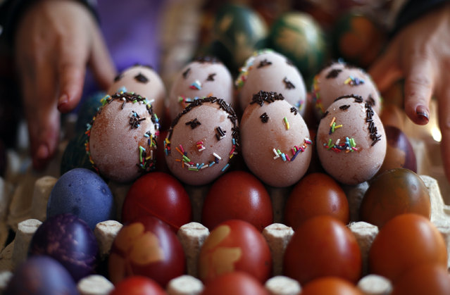 A vendor arranges hand decorated Easter eggs at Green Market, in Belgrade, Serbia, on Orthodox Good Friday, April 10, 2015. Orthodox Serbs celebrate Easter on April 12, according to old Julian calendar, and the ancient tradition of hand decorated eggs is upheld in this Orthodox Easter custom. (Photo by Darko Vojinovic/AP Photo)