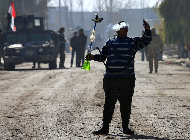 A man smokes a waterpipe on the street during a battle with Islamic State militants, eastern Mosul, Iraq, January 12, 2017. (Photo by Alaa Al-Marjani/Reuters)