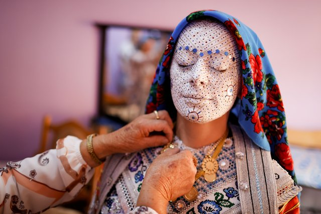 Kosovar Bosnian women help the bride Sellma Demirovic (C) to be dressed with traditional clothes on her wedding day for a traditional ceremony in the village of Donje Ljubinje, Kosovo, 14 August 2021. (Photo by Valdrin Xhemaj/EPA/EFE)