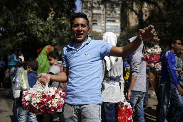 "An Egyptian street flower vender sells fresh flowers at the Giza Zoo, as the country marks Sham el-Nessim, or ""smelling the breeze"", in Giza, Egypt, Monday, April 13, 2015. (Photo by Hassan Ammar/AP Photo)"