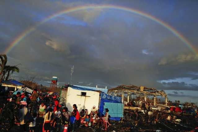 A rainbow appears above Typhoon Haiyan survivors desperate to catch a flight from the Tacloban airport November 15, 2013. (Photo by Damir Sagolj/Reuters)
