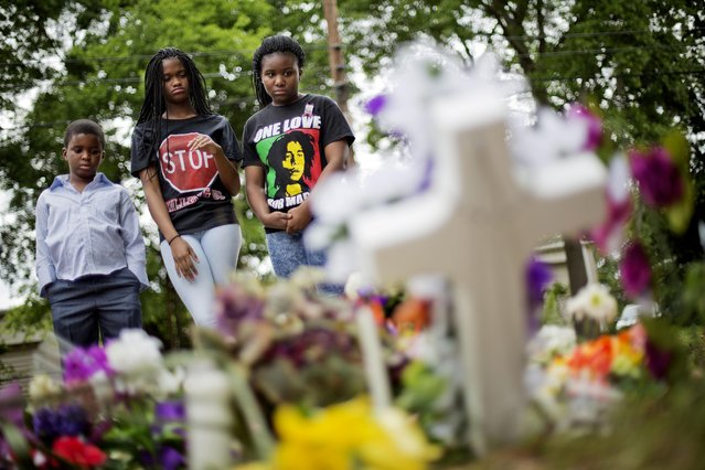 Isaiah Lewis, 7, from left, Ianna Johnson, 13, and Katelyn Robinson, 14, visit a makeshift memorial where Walter Scott was fatally shot by a white police officer after he fled a traffic stop, Sunday, April 12, 2015, in North Charleston, S.C. The officer, Michael Thomas Slager, has been fired and charged with murder. (Photo by David Goldman/AP Photo)