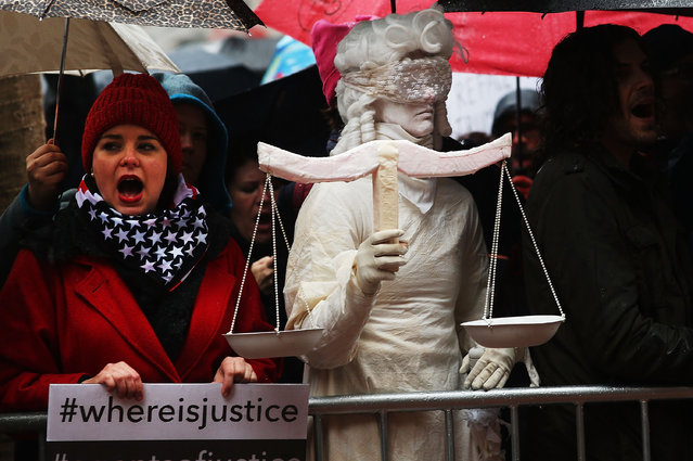 A woman dressed as Lady Justice joins over 100 protesters, many of them women, at a rally in heavy rain outside of the offices of Democratic Senators Chuck Schumer and Kirsten Gillibrand to demand that they hold up the nomination process of President Donald Trump's cabinet choices on January 24, 2017 in New York City. Numerous Trump nominees are being voted on by the Senate this week. (Photo by Spencer Platt/AFP Photo)