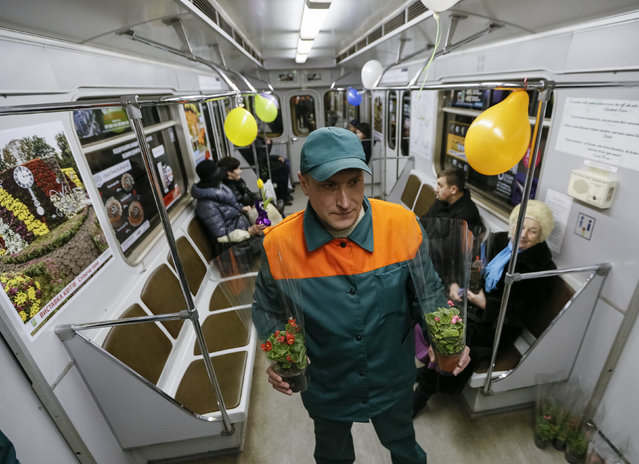 A member of Kiev's subway staff waits for female passengers in order to offer them flowers ahead of the International Women's Day in Kiev, Ukraine, March 2, 2016. (Photo by Gleb Garanich/Reuters)