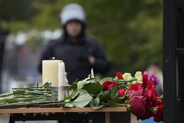 Candles and flowers are placed on a table as a police officer stands guard outside the  Perm State University following a campus shooting in Perm, about 1,100 kilometers (700 miles) east of Moscow, Russia, Tuesday, September 21, 2021. (Photo by Dmitri Lovetsky/AP Photo)