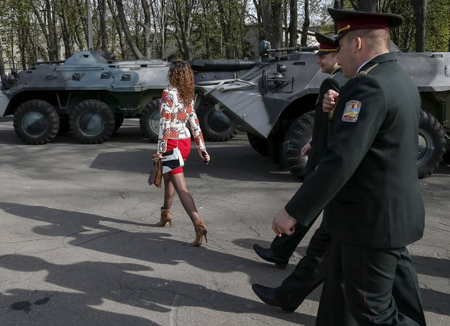A visitor and Ukrainian army officers arrive to a graduation ceremony at the National University of Defence of Ukraine in Kiev, April 24, 2015. (Photo by Gleb Garanich/Reuters)