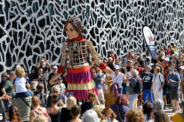 """""""Little Amal"""" is carried along the Mucem museum in Marseille, on September 22, 2021, as part of """"The walk"""", a festival of art that follows the journey of Little Amal, a giant puppet depicting a Syrian refugee girl travelling 8000km across Turkey and Europe. (Photo by Nicolas Tucat/AFP Photo)"""