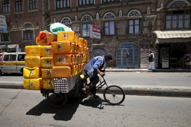 A man transports empty containers to sell on his bicycle in Sanaa, April 24, 2015. (Photo by Mohamed al-Sayaghi/Reuters)