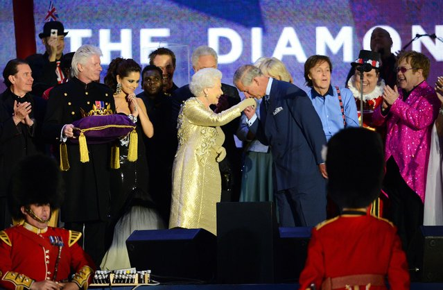 Prince Charles, Prince of Wales, kisses the hand of Britain's Queen Elizabeth II on stage as British singers Paul McCartney (3R) and Elton John (R) and other performers look on after the Jubilee concert at Buckingham Palace in London on June 4, 2012. (Photo by Leon Neal/AFP Photo)