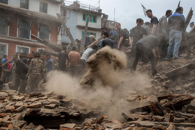 Emergency workers and bystanders clear debris while searching for survivors under a collapsed temple in Basantapur Durbar Square following an earthquake on April 25, 2015 in Kathmandu, Nepal. (Photo by Omar Havana/Getty Images)