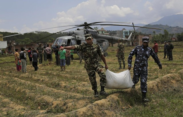 Nepalese soldiers unload relief material brought in an Indian air force helicopter for victims of Saturday's earthquake at Trishuli Bazar in Nepal, Monday, April 27, 2015. (Photo by Altaf Qadri/AP Photo)
