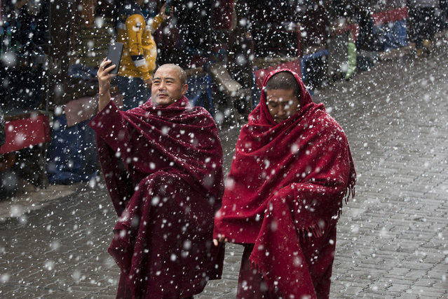 In this Wednesday, February 27, 2019, photo, an exile Tibetan Buddhist monk uses his phone camera as he walks with another in the snow in Dharmsala, India. This Himalayan region saw another snowfall on Wednesday. (Photo by Ashwini Bhatia/AP Photo)