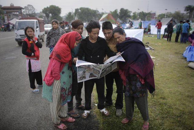 Survivors of Saturday's earthquake read newspaper at a makeshift camp in Kathmandu, Nepal, Tuesday, April 28, 2015. A strong earthquake shook Nepal's capital and the densely populated Kathmandu valley on Saturday. (Photo by Altaf Qadri/AP Photo)