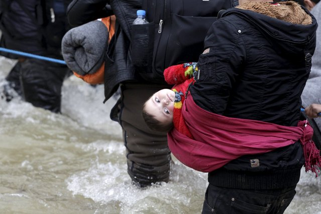 A woman carries a baby as migrants wade across a river near the Greek-Macedonian border, west of the the village of Idomeni, Greece, March 14, 2016. (Photo by Alexandros Avramidis/Reuters)