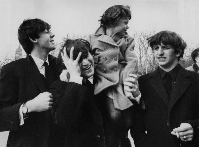 John Lennon, center, holds his forehead as 5-year-old Debbie Fyall, of London, England, sits on his shoulders, in New York, Central Park, USA, February 8, 1964. The other two members of the Beatles are Paul McCartney, left, and Ringo Starr, right. (Photo by AP Photo/The Beatles)