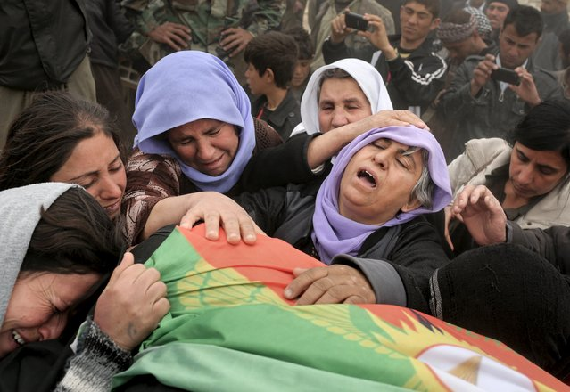 The mother of a Yazidi fighter from YBS (2nd R), who was killed during fighting with Islamic State militants, mourns with relatives over the body of her son during a funeral ceremony at a cemetery in Sinjar, March 12, 2015. YBS are a Yazidi militant group, who are fighting against Islamic State. (Photo by Asmaa Waguih/Reuters)