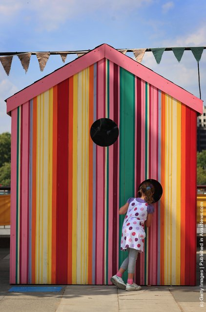A young girl peers into an installation on the South Bank