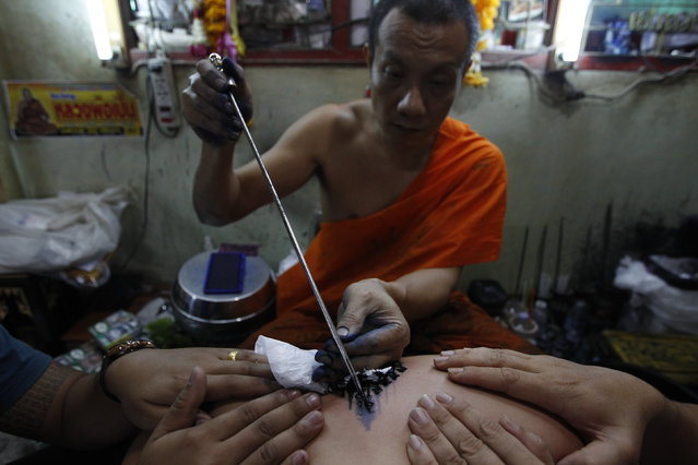 A Buddhist monk uses a traditional needle to tattoo the body of a man at Wat Bang Phra in Nakhon Pathom province on the outskirts of Bangkok, Thailand,  March 18, 2016. (Photo by Chaiwat Subprasom/Reuters)